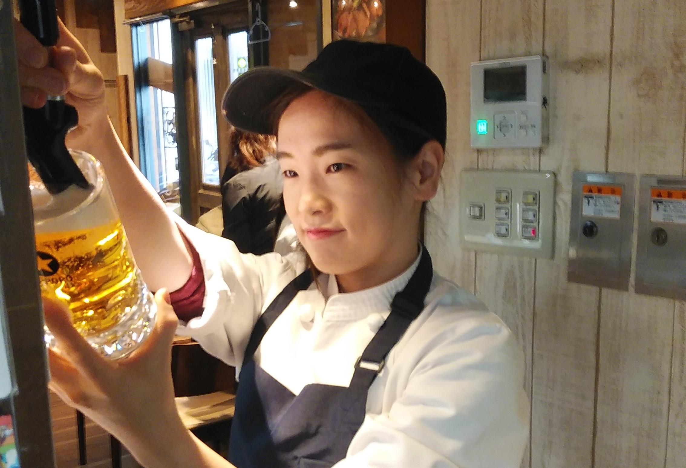 ステーキハウス ヒーローズで女性スタッフが生ビールを注いているところ