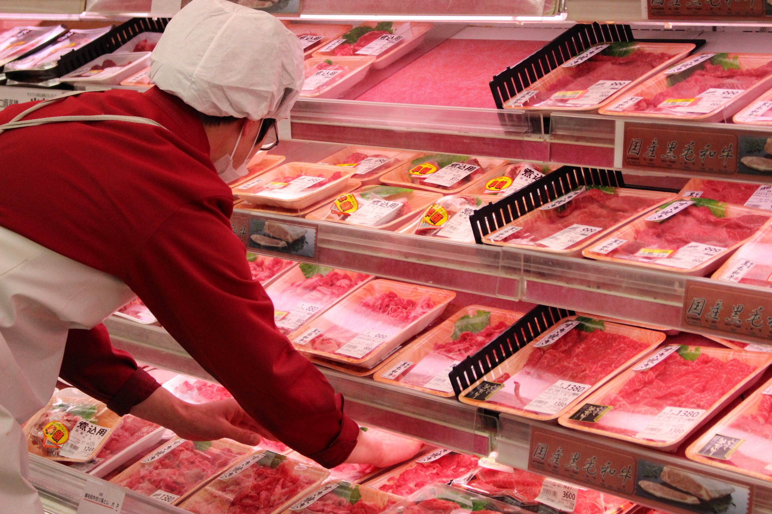 スーパーマーケットOlympicの精肉部門。肉売場でパックを陳列しているところ