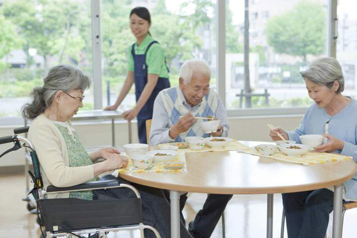 福祉施設で高齢者3名が円卓で食事を楽しんでいるシーン