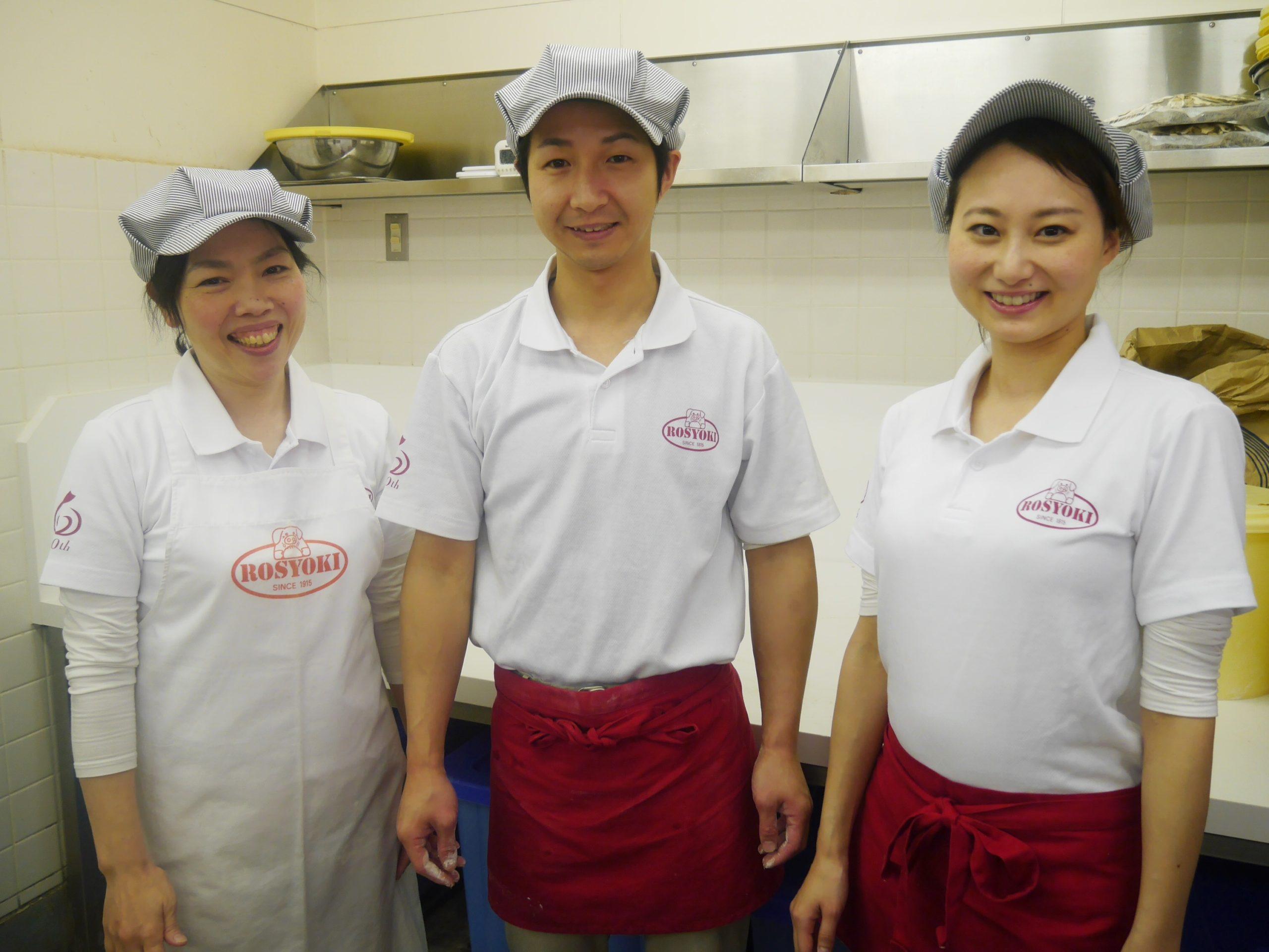 老祥記のスタッフ3名が厨房で笑顔で立っている
