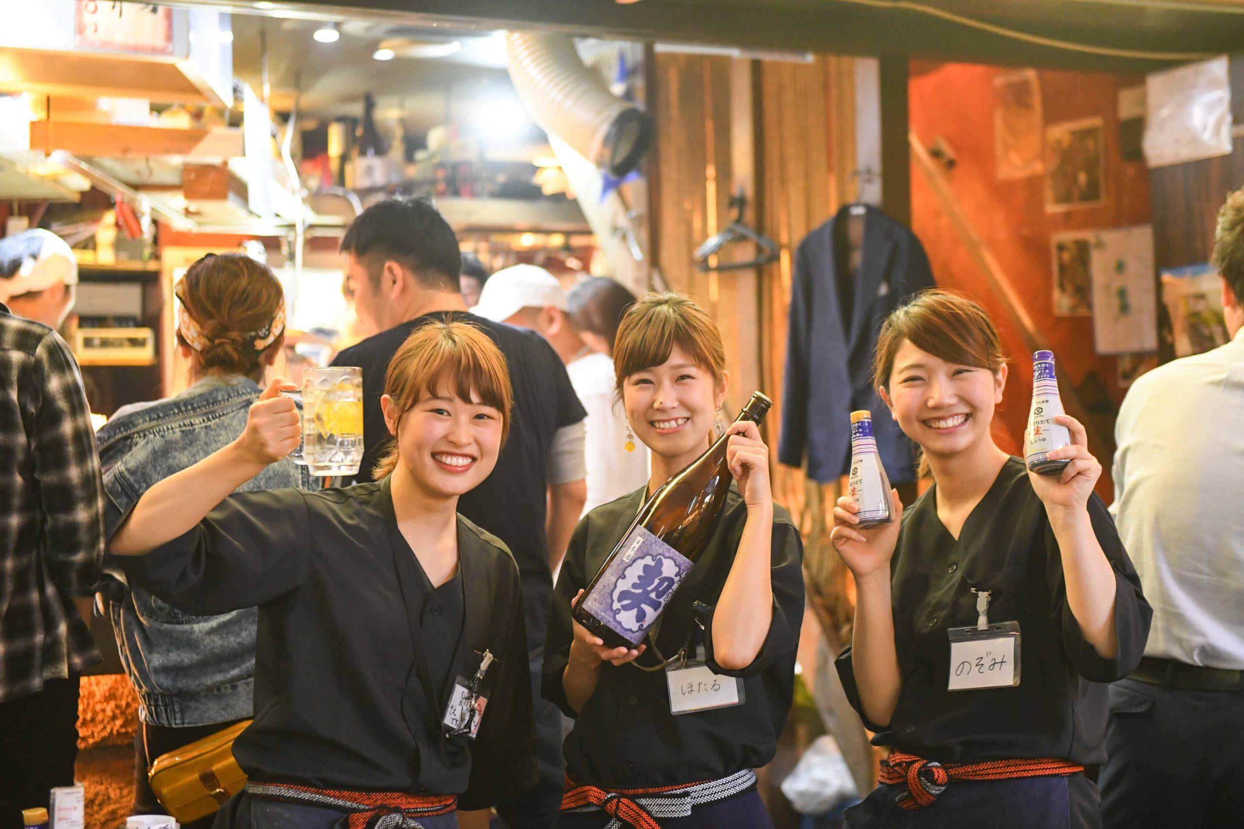 居酒屋内で笑顔でポーズをとる若手女性スタッフ3名