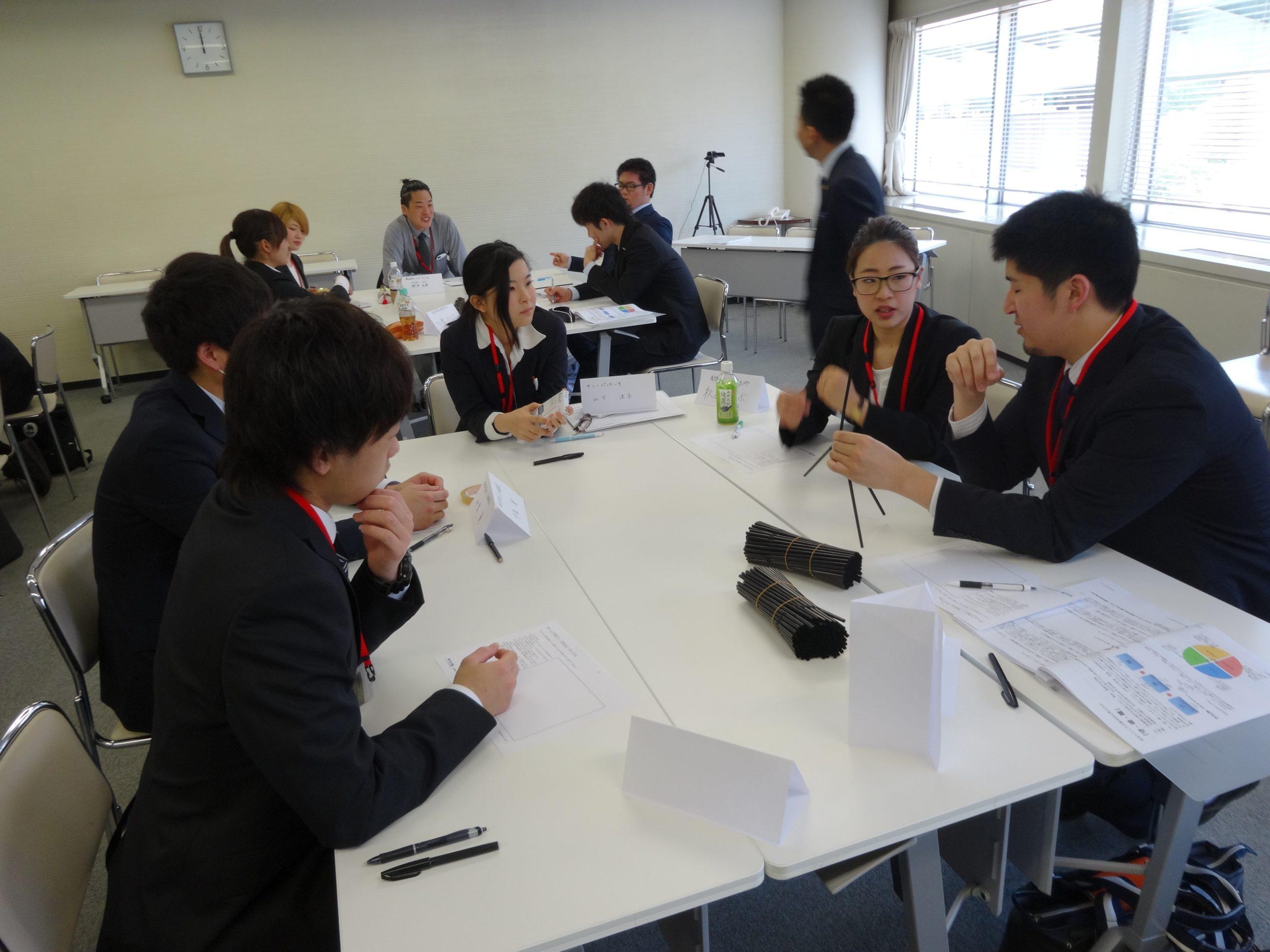秋吉しのぶさんの研修風景。グループでストロータワーを組み立てるプログラムで話し合いの風景。