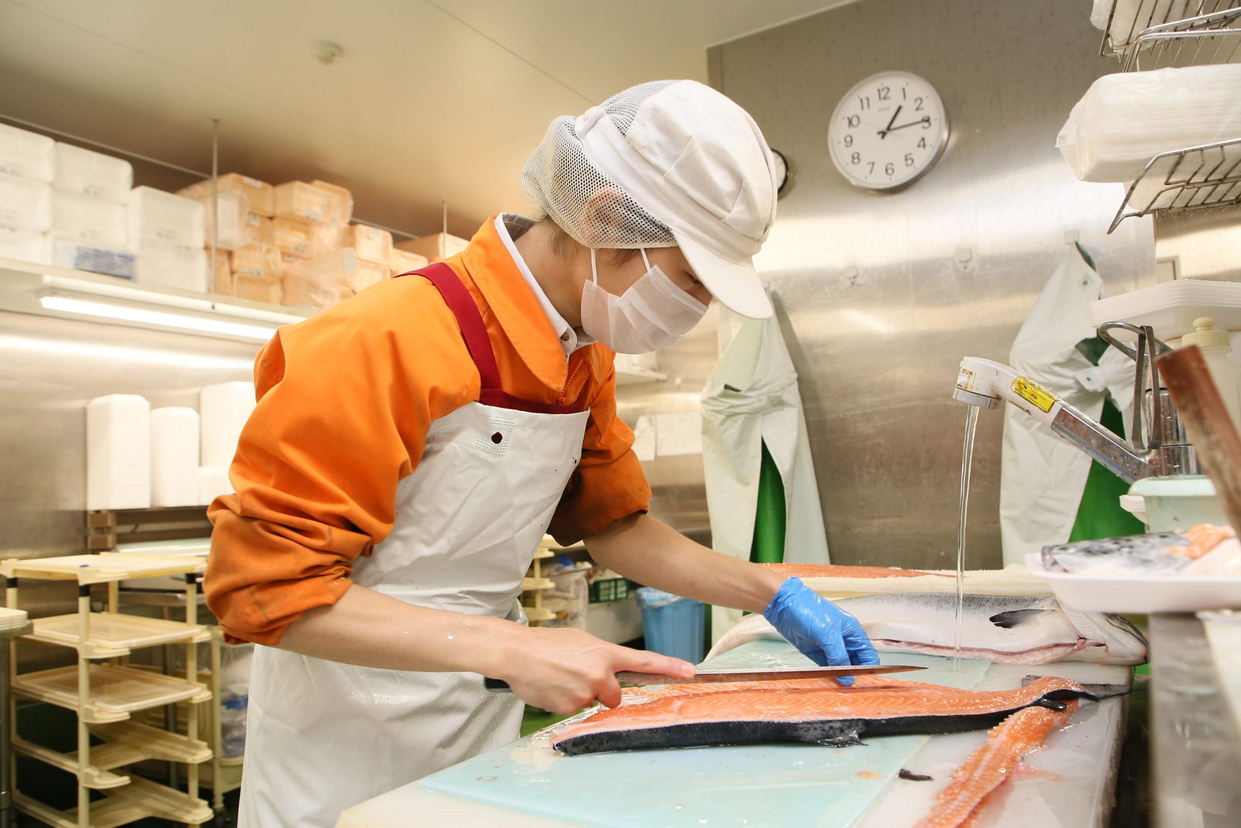 スーパーの鮮魚スタッフが魚をおろしているところ