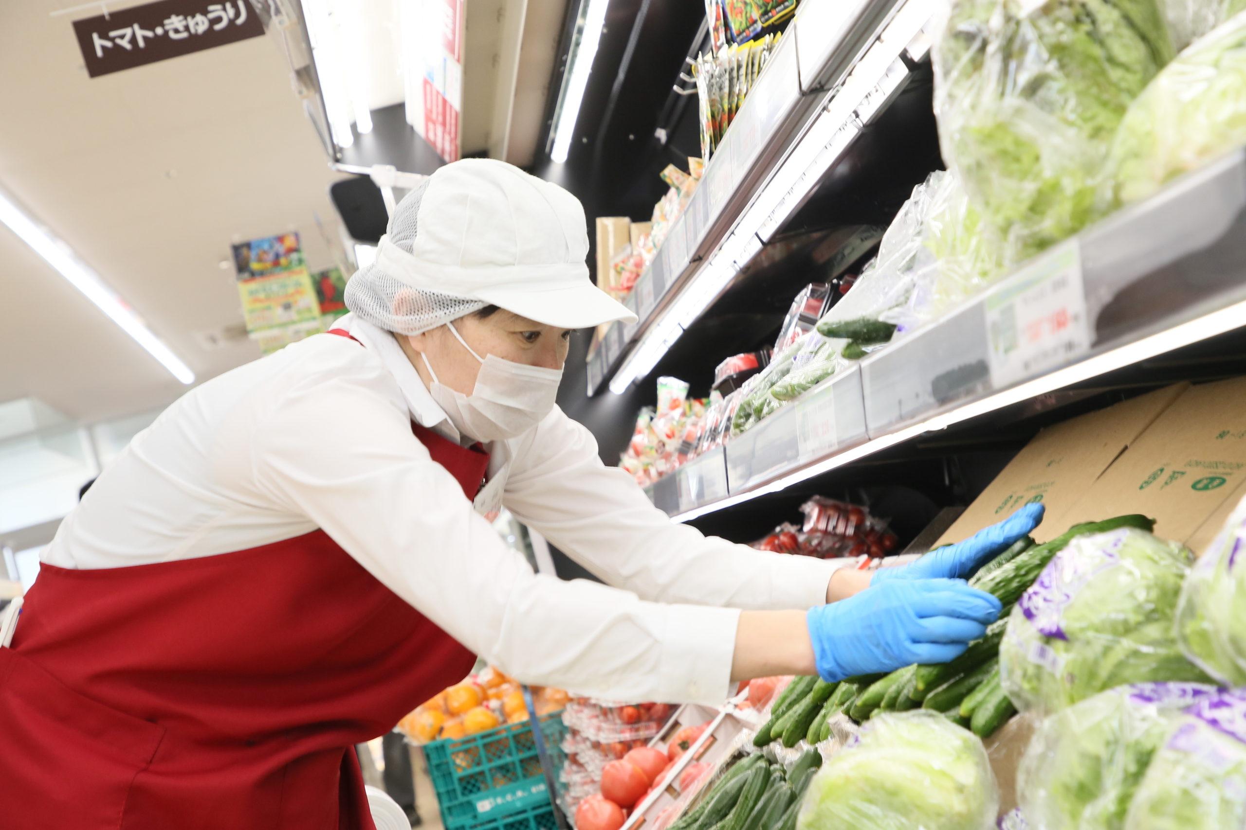 青果コーナーで野菜を並べる女性スタッフ