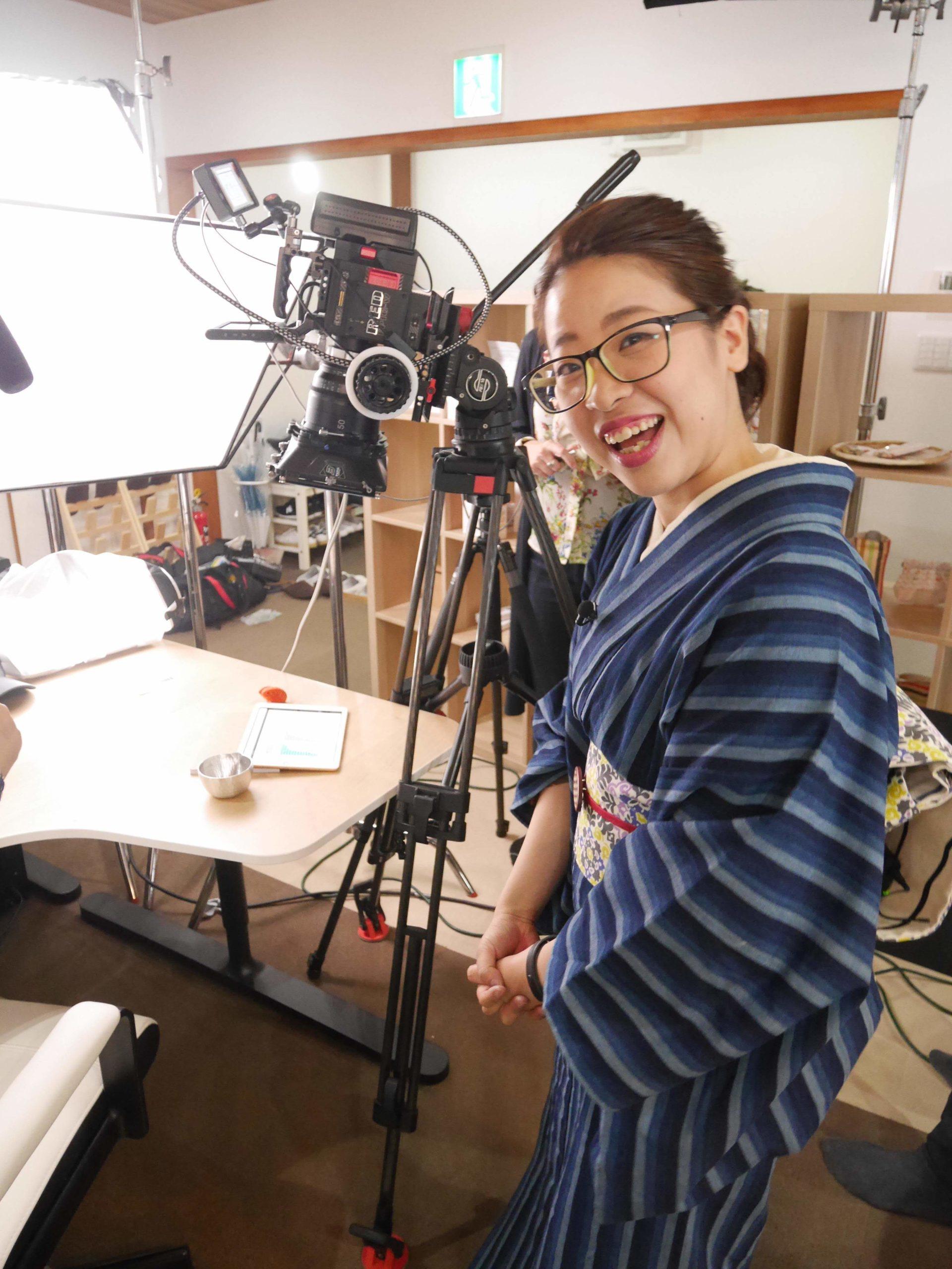 仕事中の秋吉しのぶさん。着物姿でカメラと一緒に。
