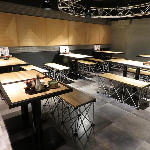 【炭火串焼 鬼灯】打ちっぱなしの床に木のテーブルがスタイリッシュな店内写真