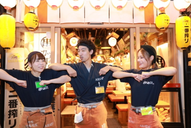 串カツあらたの店頭で腕を開くポーズで笑顔で並ぶ楽しそうな男女3人スタッフ