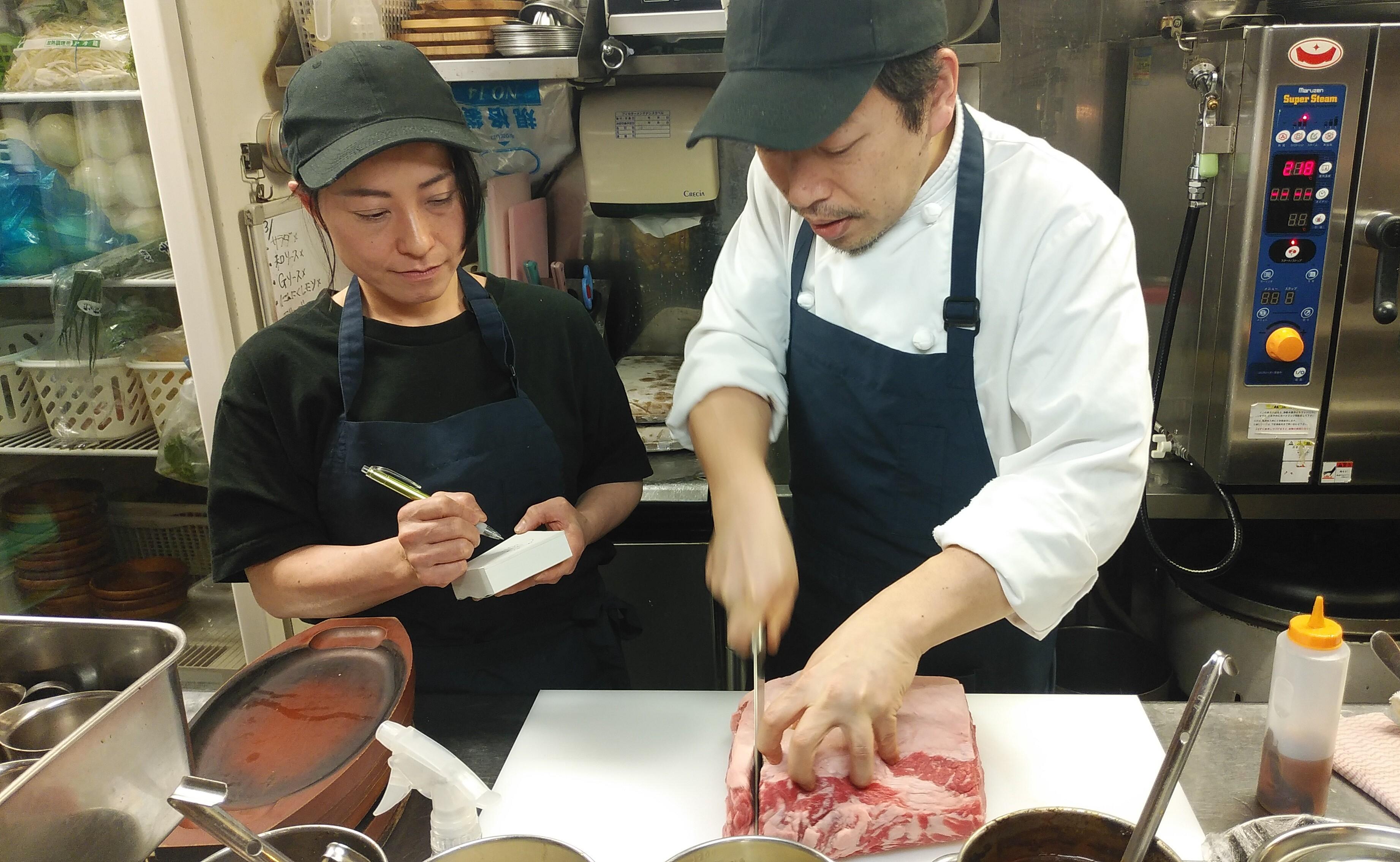 先輩スタッフが肉の塊をカットしながら若手を指導しているところ