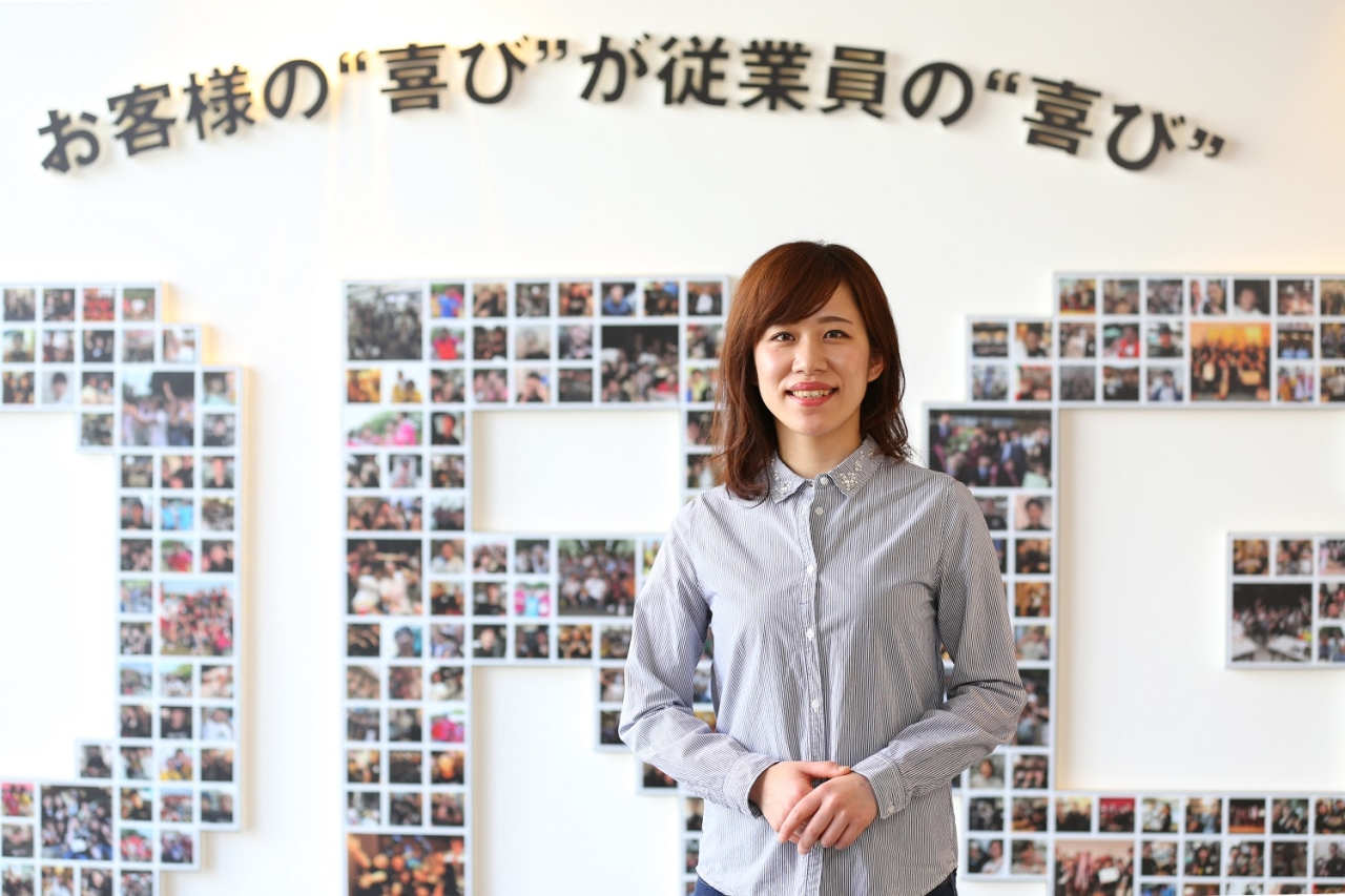 女性スタッフ看板前での写真