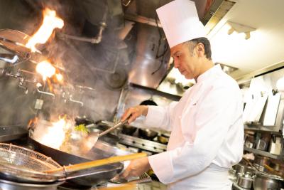 火が出る鍋を振るう料理人