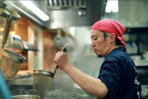天下一品のキッチンでゆでた麺をざるで引き上げる男性スタッフ