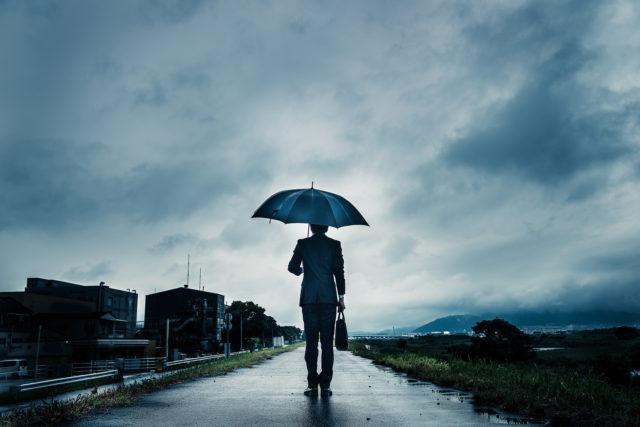 哀愁を漂わせ、雨の中を歩く男
