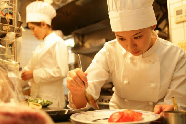 女性の料理人が料理の仕上げを行なっている