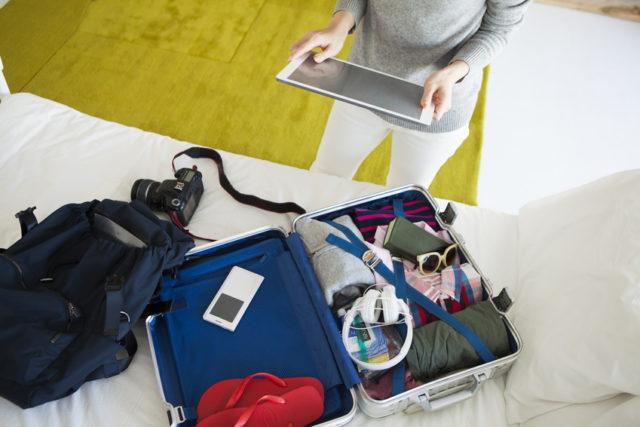旅行バッグとベッドの隣に立つ女性