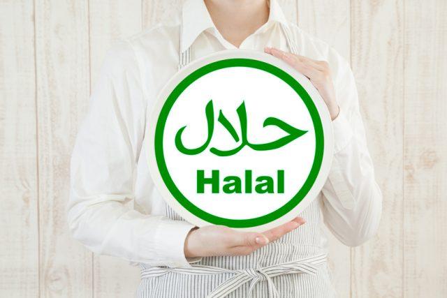 両手でHalalと書かれたボードを持っている女性の画像