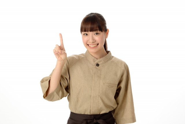 茶色の服を着たポニーテルの女性が右手の人差し指を立てて立っている写真。