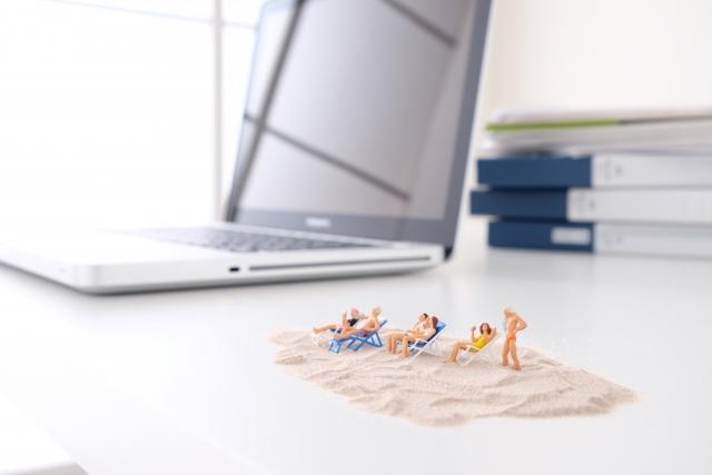 デスクの上のノートパソコンをバックに、浜辺をイメージした砂の上で休暇・バカンスを楽しむのミニチュアの人形たち