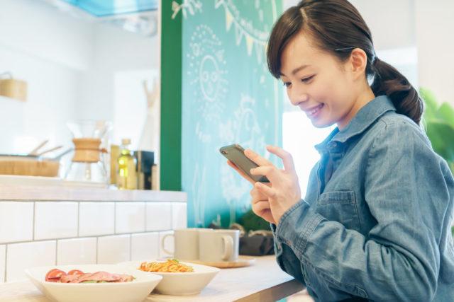 青いシャツを着たポニーテールの女性が、料理の乗ったカウンターで両手に持ったスマートフォンを見ている様子。
