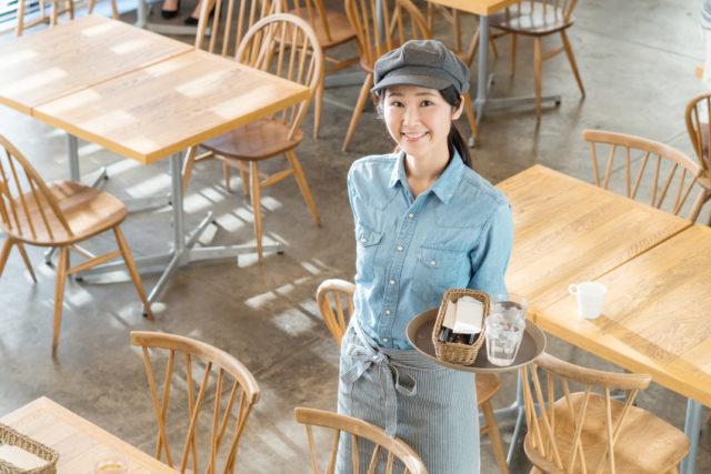 テーブルとイスが並んでいるホールで、青いシャツに縦じまのエプロン、グレーの帽子をかぶった女性が左手にコップ2つとカトラリーケースの乗ったお盆を持っている様子。