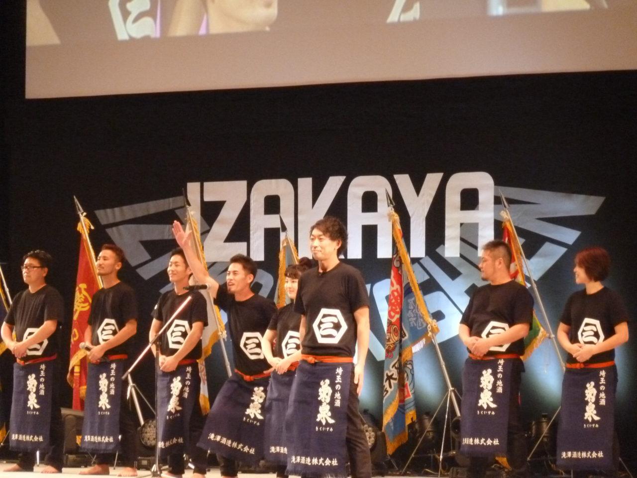 8名の男女が並んでおり、左から4番目の男性が右手を上げマイクの前で宣誓を行っている。