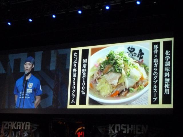 スクリーンに「化学調味料無使用」「豚骨×鶏ガラのダブルスープ」「国産野菜100%」「たっぷり野菜230グラム」とちゃんぽんの紹介と写真が映し出され、男性スタッフがプレゼンテーションをしている。