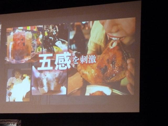 スクリーンにドリンクや肉にかぶりつく写真など6枚と「五感を刺激」と書かれている