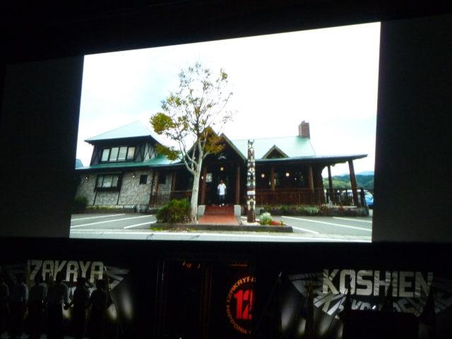 正面には1本の木とトーテンポールが立っており、緑の屋根と石造りと木造りのお店の外観がスクリーンに写されている。