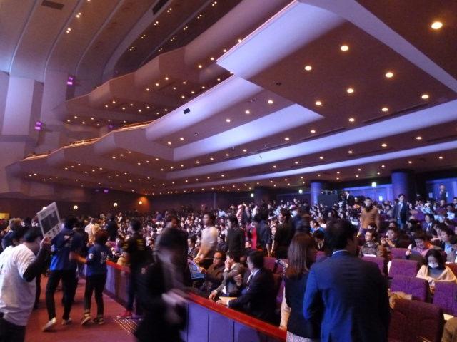 高い天井のホールにおびただしい数の人が続々と入場してくる様子。