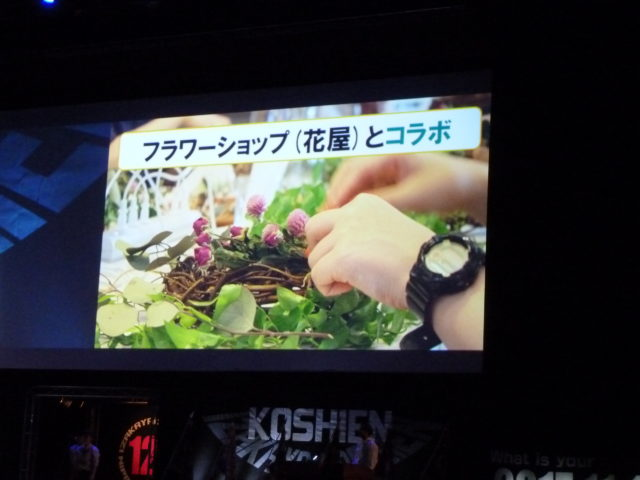 リースつくりをしている写真に「フラワーショップ(花屋)とコラボ」と書かれているスクリーン上のスライド。