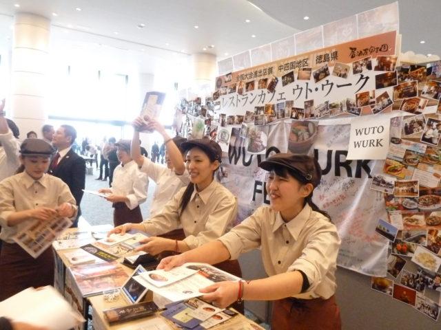 店舗ブースで白シャツ、赤いエプロンに茶色の帽子姿の女性スタッフ5人がチラシを配っている様子。