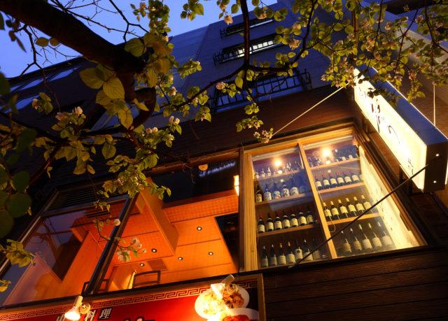 開放感のある大きな窓にワインがずらりと並んでいる棚が見えているお店の外観の写真