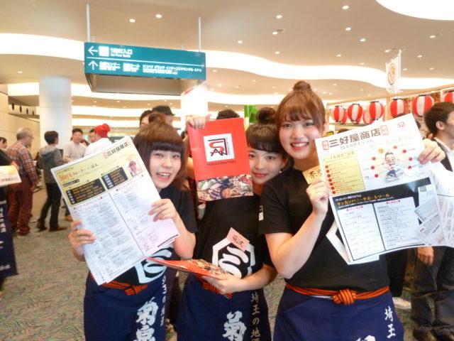 ロビーで「三好屋商店」のチラシを持った黒シャツに青いエプロン姿の女性スタッフ3人。