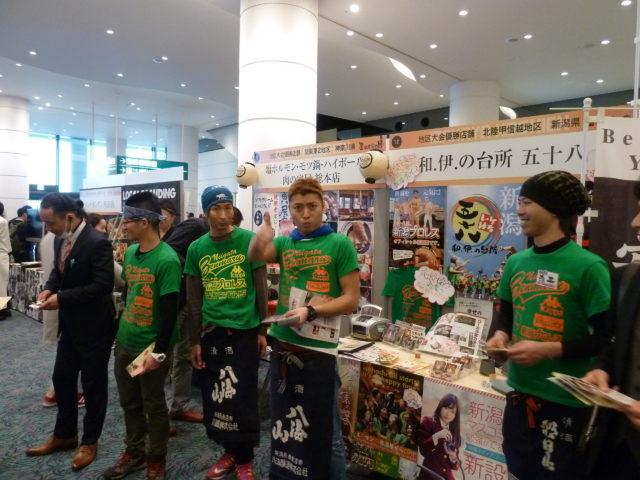 「和.伊.の台所 五十八」の男性スタッフ4名が店舗改善ツールのプリントを配布している様子。