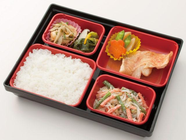 4つの赤いブロックで分かれたお弁当には花形にくりぬかれた人参などの野菜や魚が入っている