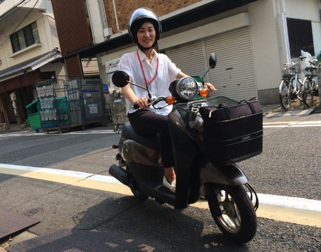 女性がバイクにまたがり、笑顔で訪問サポートに向かっている様子。