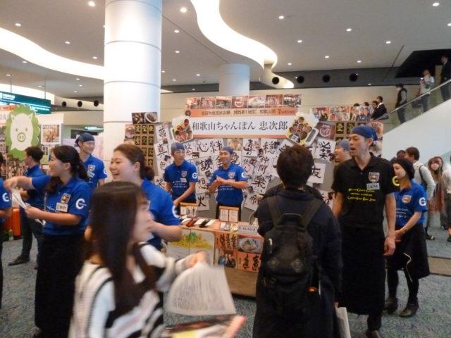 青いシャツを着た「和歌山ちゃんぽん 忠次郎」のスタッフがチラシを配ったり笑顔で接客している様子。