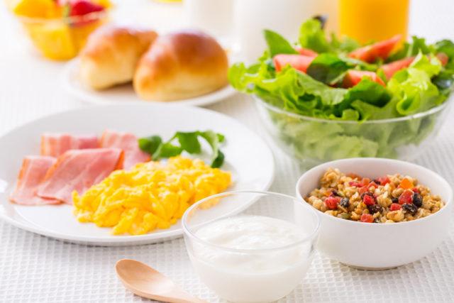白いテーブルクロスの上に、奥から果物、ジュース、パン、サラダ、ベーコン、卵、シリアル、ヨーグルトが置かれている。朝食のイメージ。