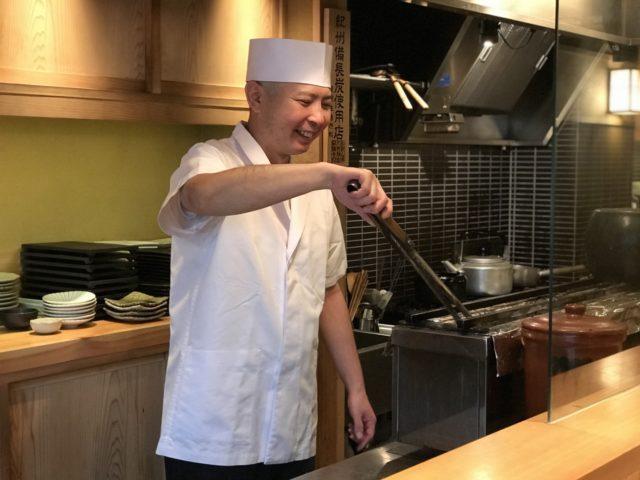 カウンターの中で炭を火箸で触っているかっぽう着姿の加藤さんの写真