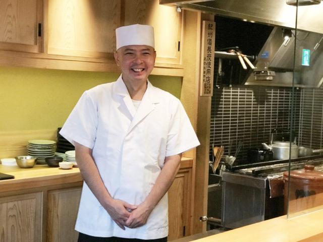 カウンターの中でかっぽう着姿の加藤さんが両手をそろえてにこやかに立っている写真