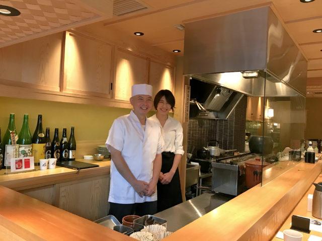 カウンターの中にかっぽう着姿の加藤さん(左)と白シャツに黒いエプロン姿のパートナーの女性(右)が並んで立っている写真