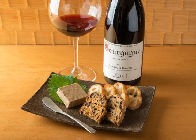 木のテーブルの上に、赤ワインの入ったワイングラスとワインのボトル。手前には四角いお皿にレバーのパテとバゲットが盛られている写真