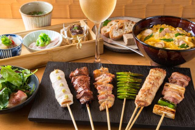 木箱に入った小鉢の料理や、サラダ、バゲット、四角いお皿に盛り付けられた6種類の串焼き、親子丼がテーブルに置かれており、中心にはワインが置かれている写真