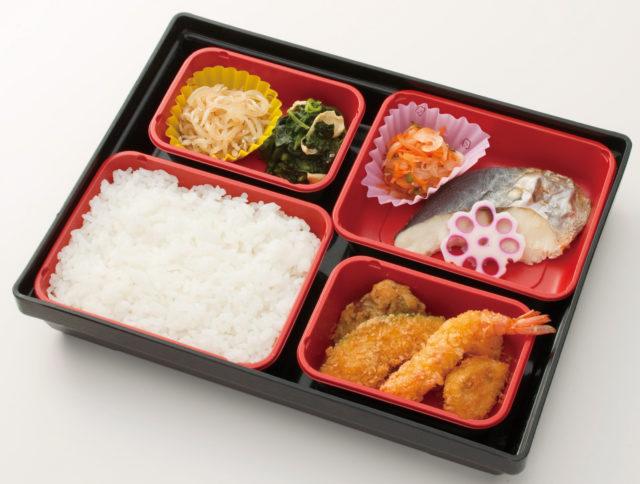 4ブロックに分かれている栄養コントロール食お弁当の例。右上には花をあしらったようなレンコンが乗ったお魚と付け合わせ1品、右下にはフライが4品、左上にはお野菜が2品、左下には白米。