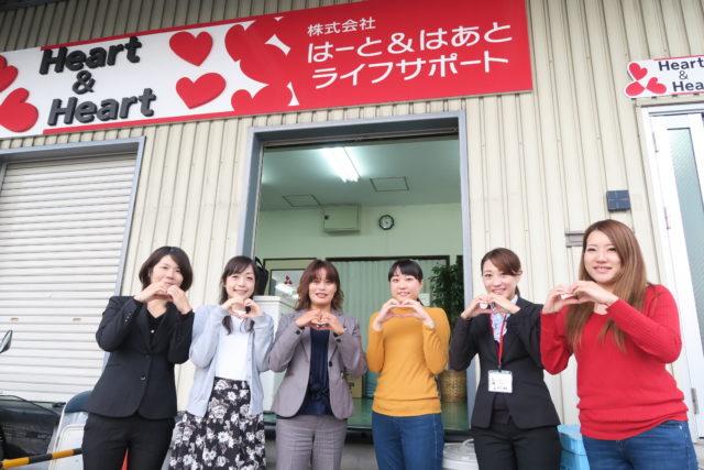 「株式会社はーと&はあとライフサポート」の会社の前で、女性6名が各々手でハートを作って並んでいる様子。