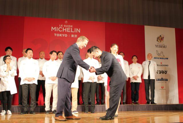 ミシュランガイド総責任者 マイケル・エリス氏と握手をする黒いスーツ姿の川田智也さん。
