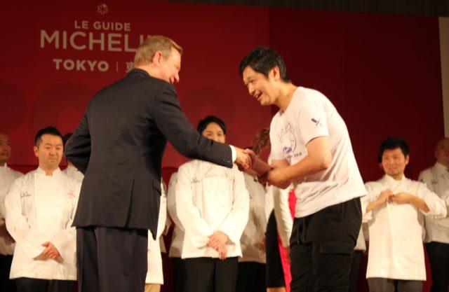 ミシュランガイド総責任者 マイケル・エリス氏と握手をするTシャツ姿の川手寛康さん。