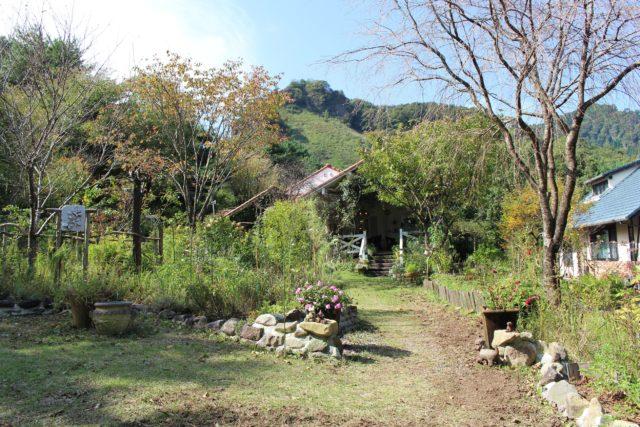 緑豊かな山々の中に青い屋根の家屋が写っている写真