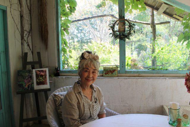 窓際の丸テーブルの席に、エプロン姿の白髪の女性オーナーが笑顔で座っている写真
