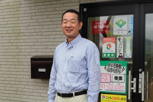 会社の入り口の前で青いシャツの男性が立っている写真