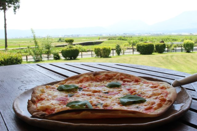 テラス席に置かれた、自家製のピザの写真。